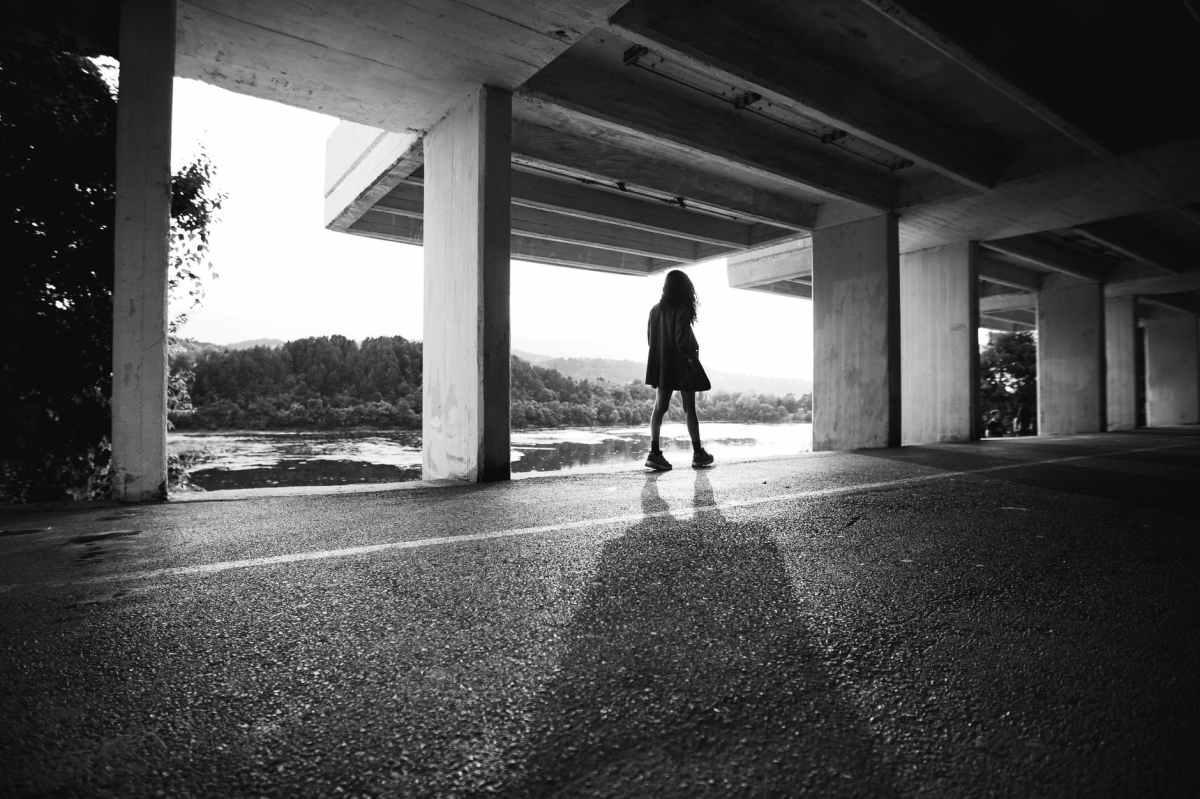 grayscale photography of woman in a parking lot